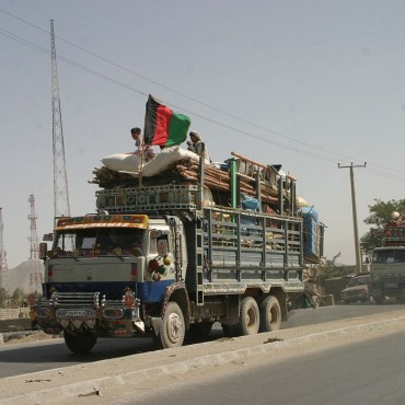 Afghans who were repatriated are arriving to Afghanistan in a truck with an Afghan flag on it